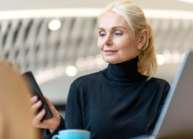 Older business woman working on laptop and smartphone while having coffee