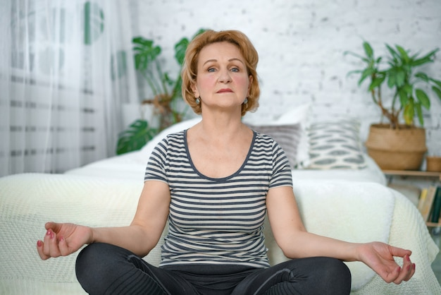 An older calm woman meditates in the lotus position at home