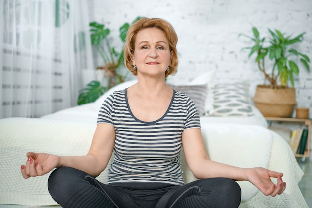 An older calm woman meditates in the lotus position at home.