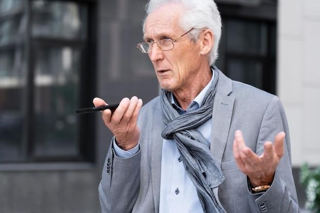 Uomo più anziano casual in città che parla su smartphone
