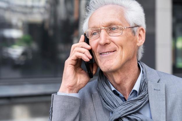スマートフォンで話している街のカジュアルな年配の男性