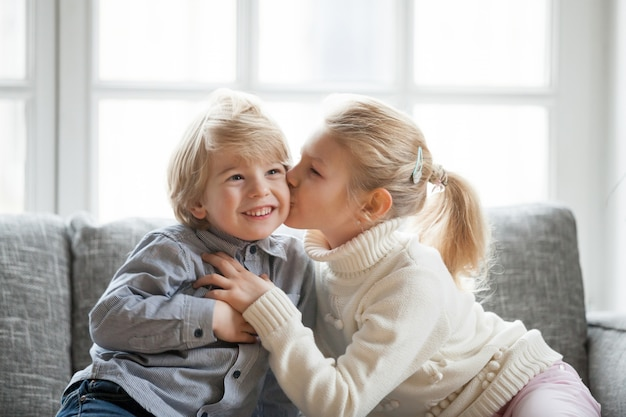 Older child sister embracing kissing little younger brother at home