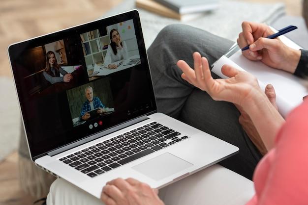 Пожилая пара дома на диване во время видеозвонка на ноутбуке