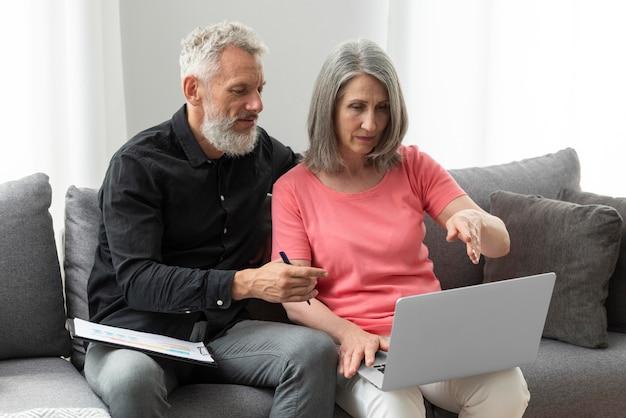 Пожилая пара дома на диване, используя ноутбук