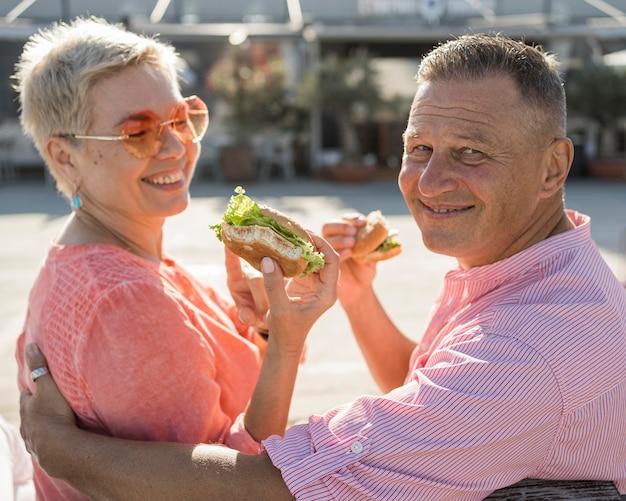 素敵なハンバーガーを楽しんでいるビーチで年配のカップル