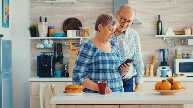 キッチンでスマートフォンを使用して家族とビデオチャット中の年配のカップル。祖父母のオンライン会話。モバイルアプリを使用して定年の現代技術を持つ高齢者