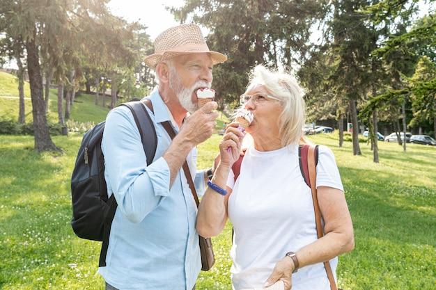 Пожилая пара ест мороженое в парке