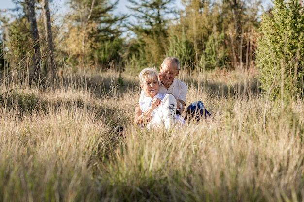 Older couple embracing sitting on the ground among tall grasses at sunset while the sun shines on them from behind.