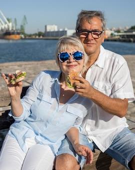 屋外で一緒にハンバーガーを楽しんでいる年配のカップル