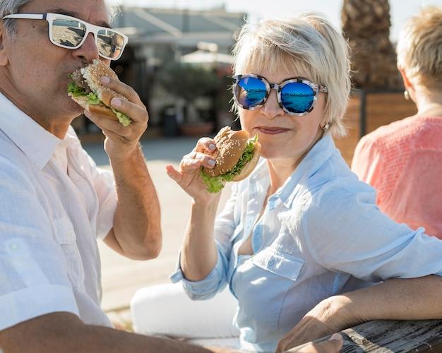 屋外でハンバーガーを楽しんでいる年配のカップル