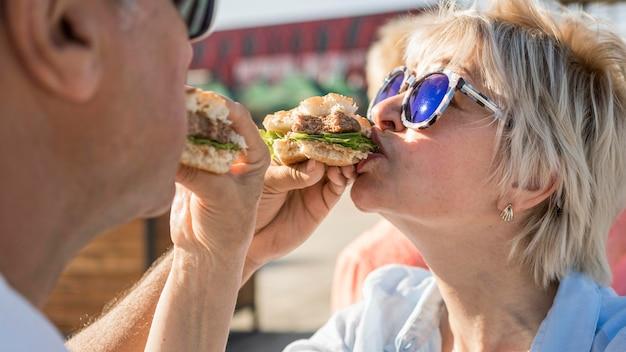 屋外でハンバーガーを食べることを楽しんでいる年配のカップル