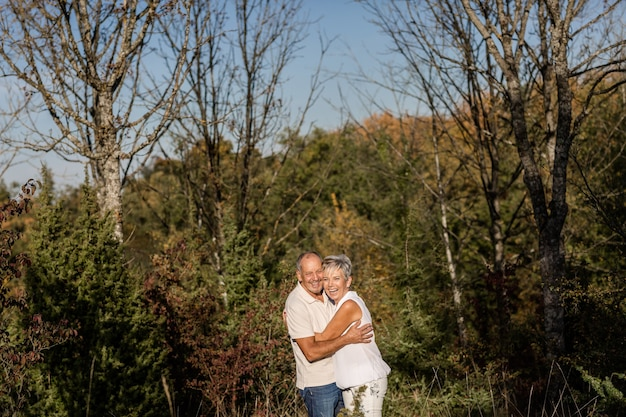 Older couple happily embracing among trees in the forest during a sunset walk.