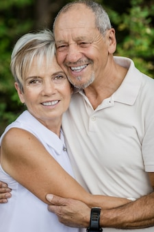 Older couple happily embracing in the woods during a walk