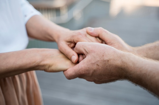 Older couple holding hands together outdoors