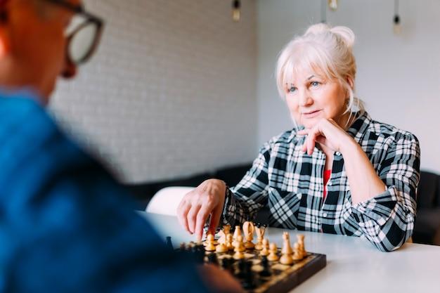 Пожилые пары в отставке дома, играя в шахматы