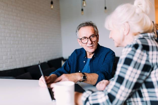Пожилые пары в отставке дома, используя ноутбук