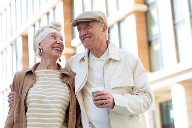 Coppia di anziani all'aperto in città con una tazza di caffè