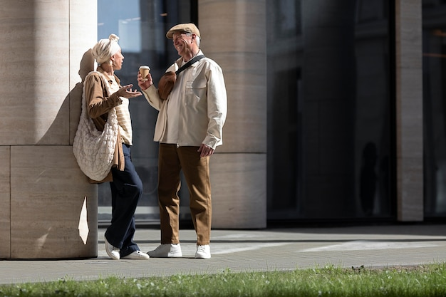 Older couple outdoors in the city with a cup of coffee