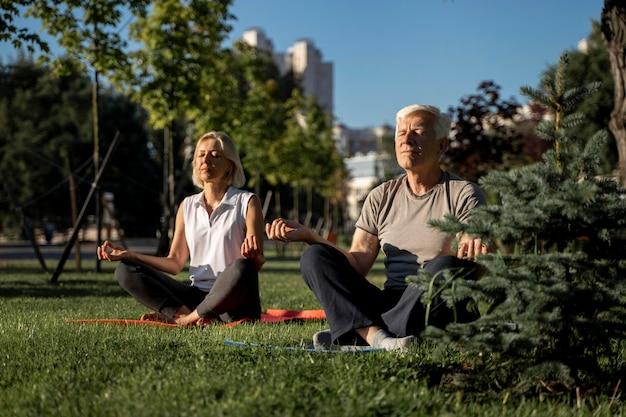 外でヨガを練習している年配のカップル