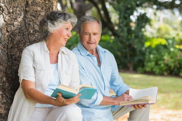 나이 든 부부 함께 책을 읽고 나무 줄기에 앉아