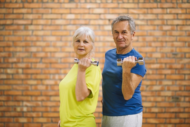 Older couple working out in gym