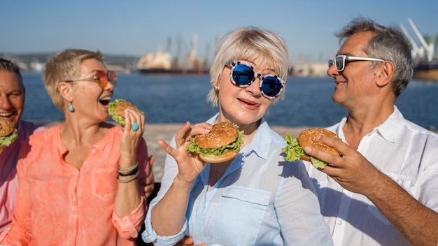 Coppie anziane in spiaggia gustando hamburger insieme