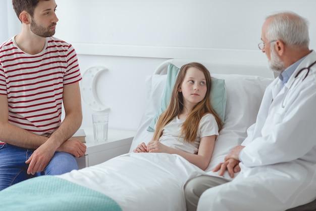 治療のために若い病気の患者を準備する年上の医者