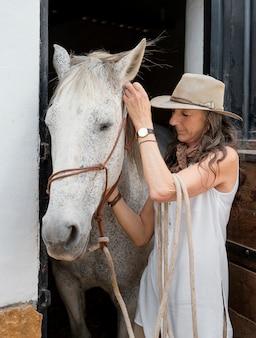 牧場で彼女の馬と年上の女性農夫