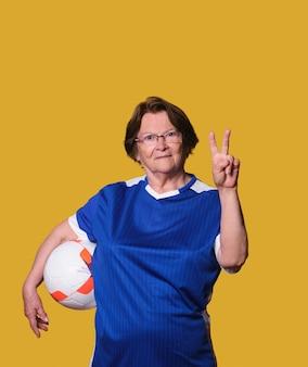 나이가 많은 여성 축구 팬이 그녀의 손가락으로 승리 제스처를 만듭니다.