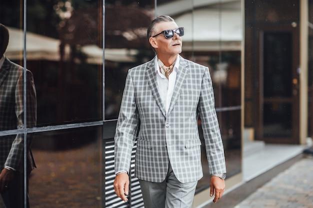 Пожилой великолепный мужчина идет по улице в стильном костюме.