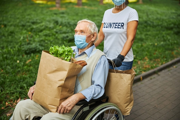 Older male in medicine mask holding paper shopping bag on the legs