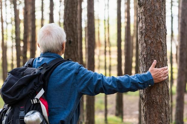 森の中をバックパッキングしながら景色を眺めながら年配の男性