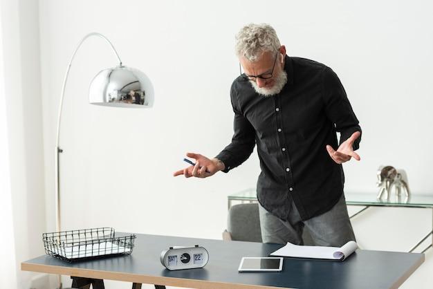Пожилой мужчина дома с помощью планшетного пк