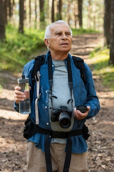 Older man backpacking in nature with camera and water bottle