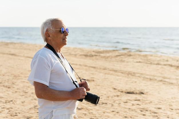 Uomo anziano in spiaggia con la macchina fotografica