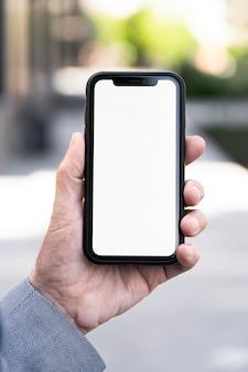 Uomo anziano in città con in mano uno smartphone