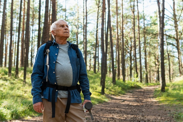 Older man exploring nature with backpack