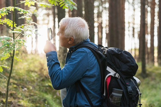 Older man exploring nature with magnifying glass