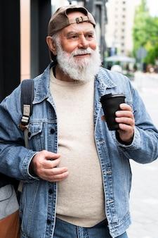 都会の屋外でコーヒーを飲む老人