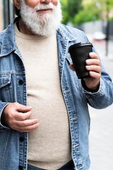 Uomo anziano che beve una tazza di caffè all'aperto in città