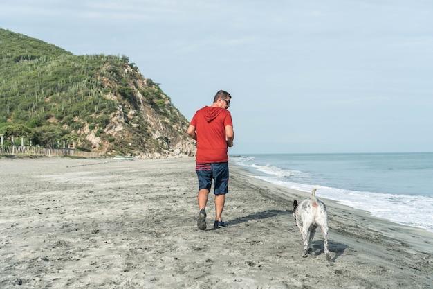 아침에 해변에서 개와 즐거운 시간을 보내는 노인