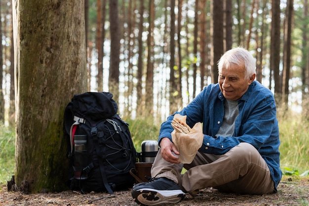 Older man having a snack outdoors in nature