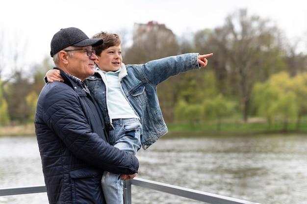 湖の近くの公園で孫を抱いている年配の男性