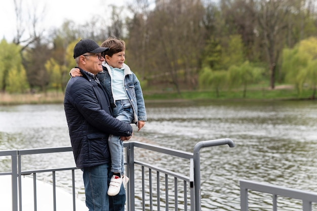 Older man holding his grandson in the park near the lake