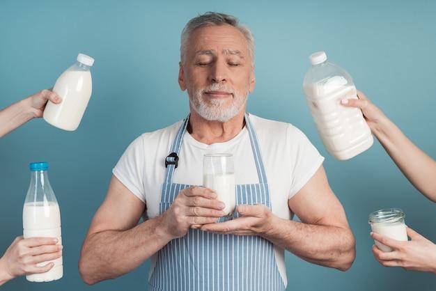 年上の男は彼の手にミルクのガラスを持っています