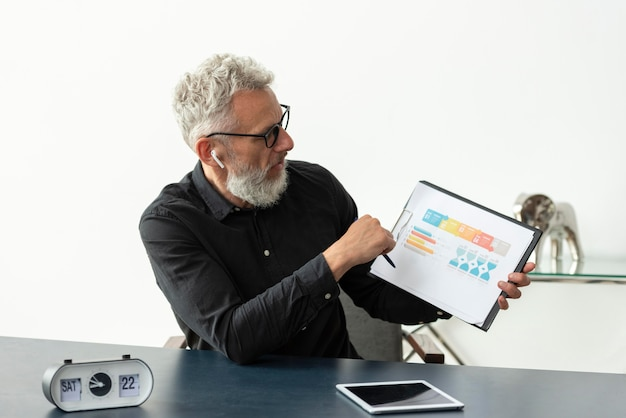 Older man at home showing graph on notepad with tablet on desk
