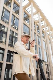 Пожилой мужчина в городе с электросамокатом с помощью смартфона Бесплатные Фотографии