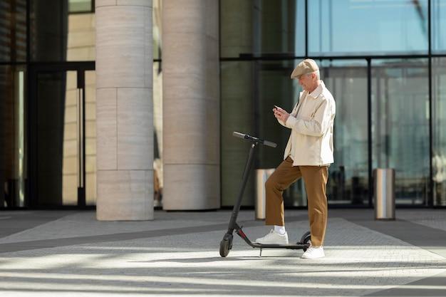 Пожилой мужчина в городе с электросамокатом с помощью смартфона