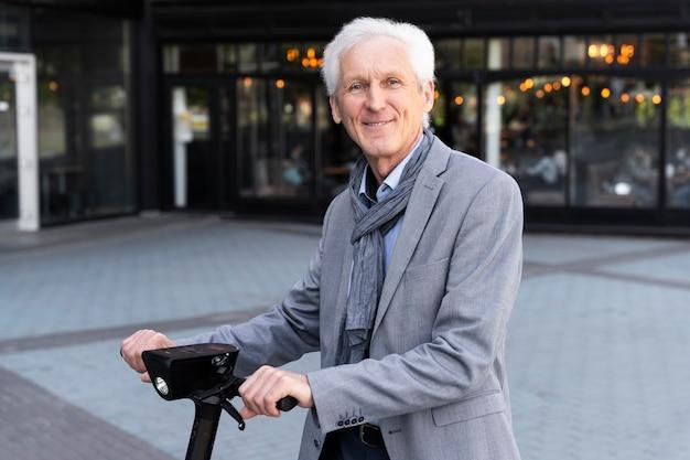 Пожилой мужчина в городе с электросамокатом