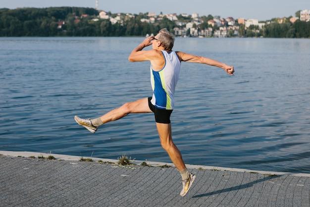 Пожилой мужчина занимается бегом на свежем воздухе. фото высокого качества